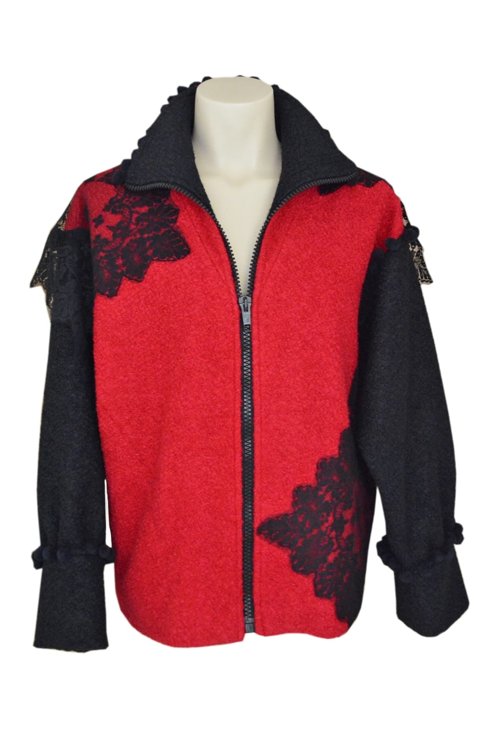 Two-tone red and black boiled wool jacket with zipper on the front and embellished with square chantilly lace patterns. Collar and handles underlined with black pompoms.