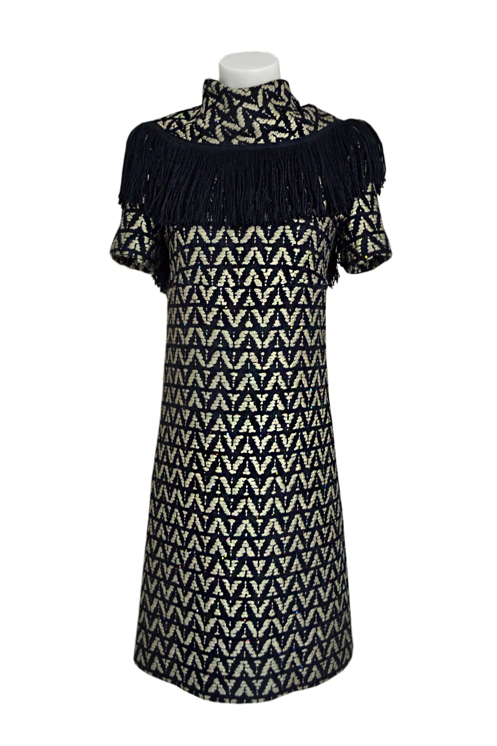 Short-sleeved dress with high neck. Black fringed neckline front and back. Beige and black tweed with geometric shapes.