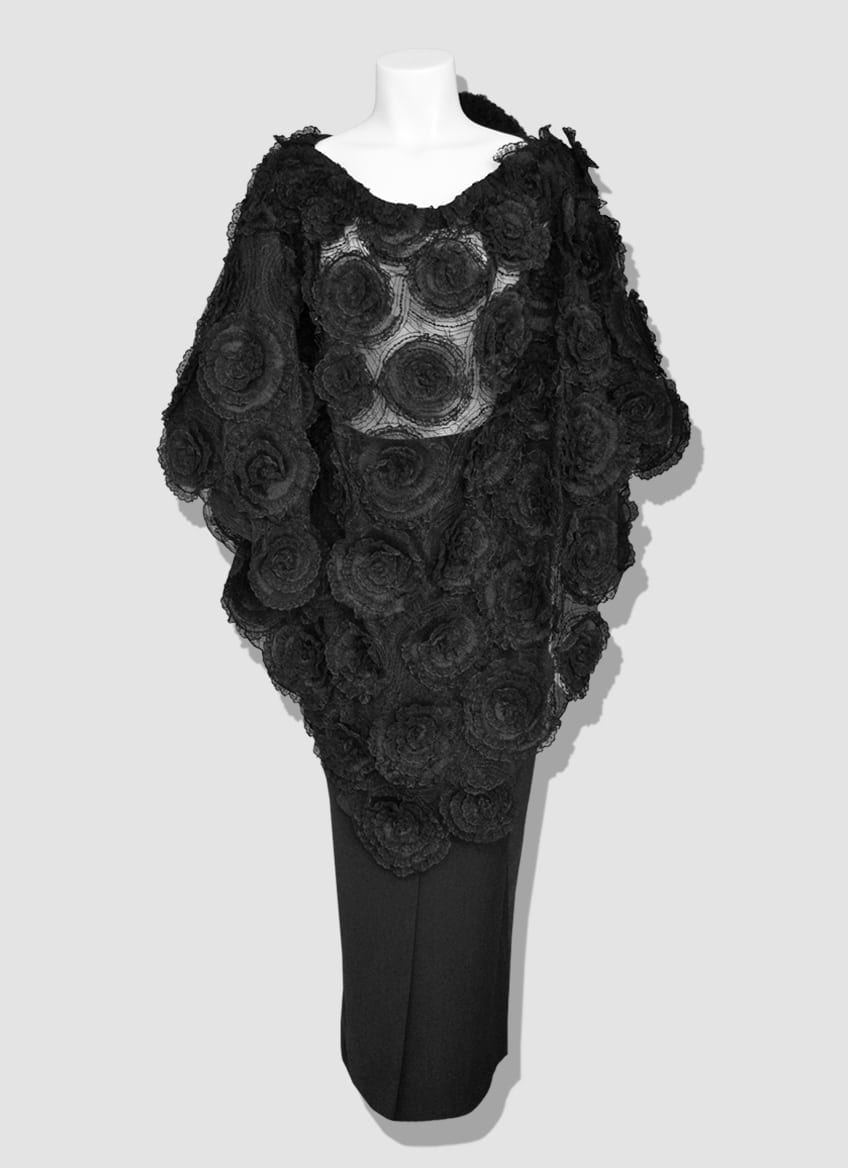 Black lace poncho with large roses in lace and bat sleeves. Mid-length skirt. An elegant and original outfit that will subtly reveal your body curves. Let your femininity speak with this silhouette signed Erik Schaix Paris.