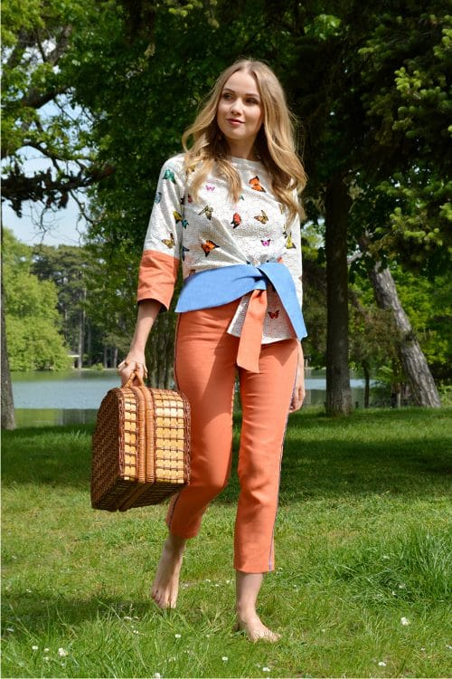 Orange pants and white top with butterflies from the French fashion designer Erik Schaix.