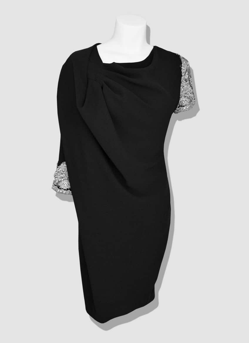 Draped black crepe cocktail dress with asymmetrical embroidered lace sleeves.
