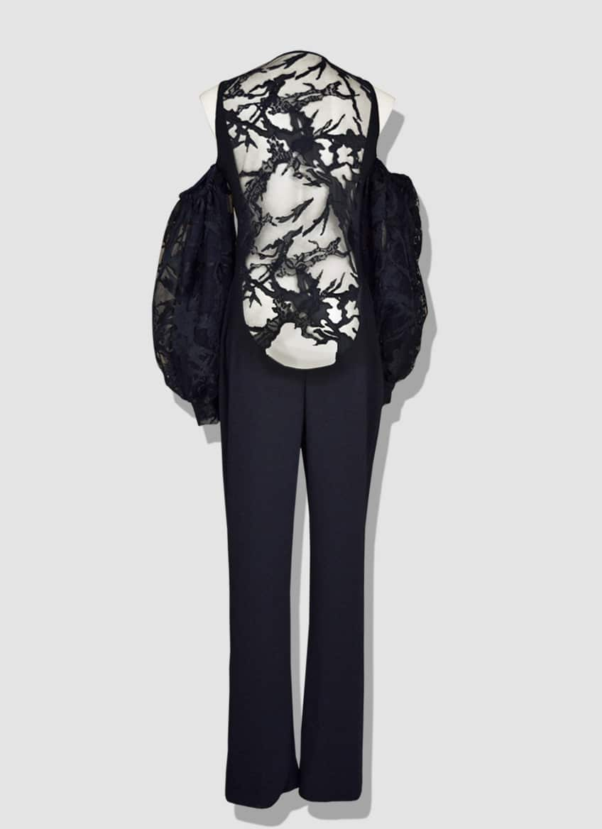 Backless jumpsuit in black lace. Crepe set with a very large pair of lace sleeves.