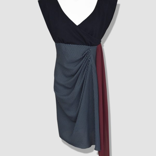 Robe à pois sans manche. Corsage en jersey coupée sous la poitrine accompagnée d'une jupe en drapée et d'un pan en crêpe georgette.