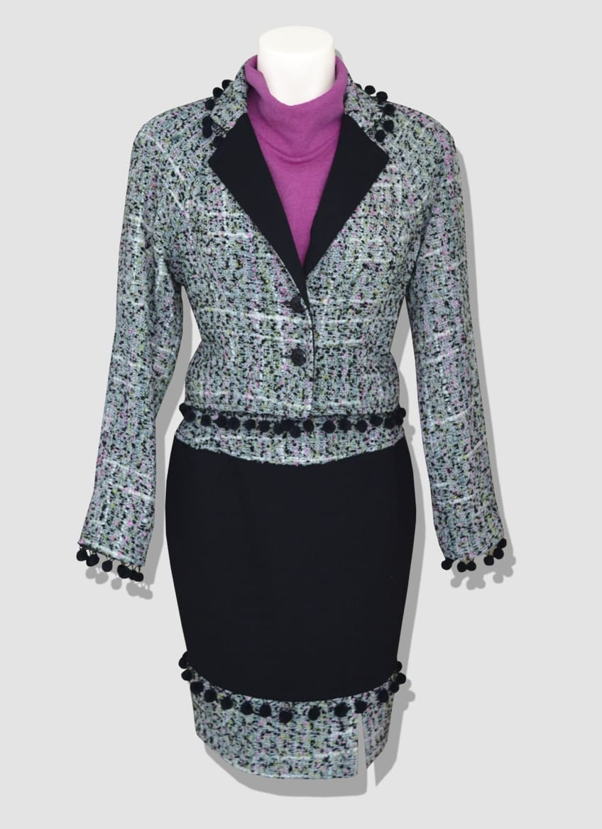 Colored tweed suit highlighted with small black pompoms. Short split skirt and fuchsia turtleneck sweater.