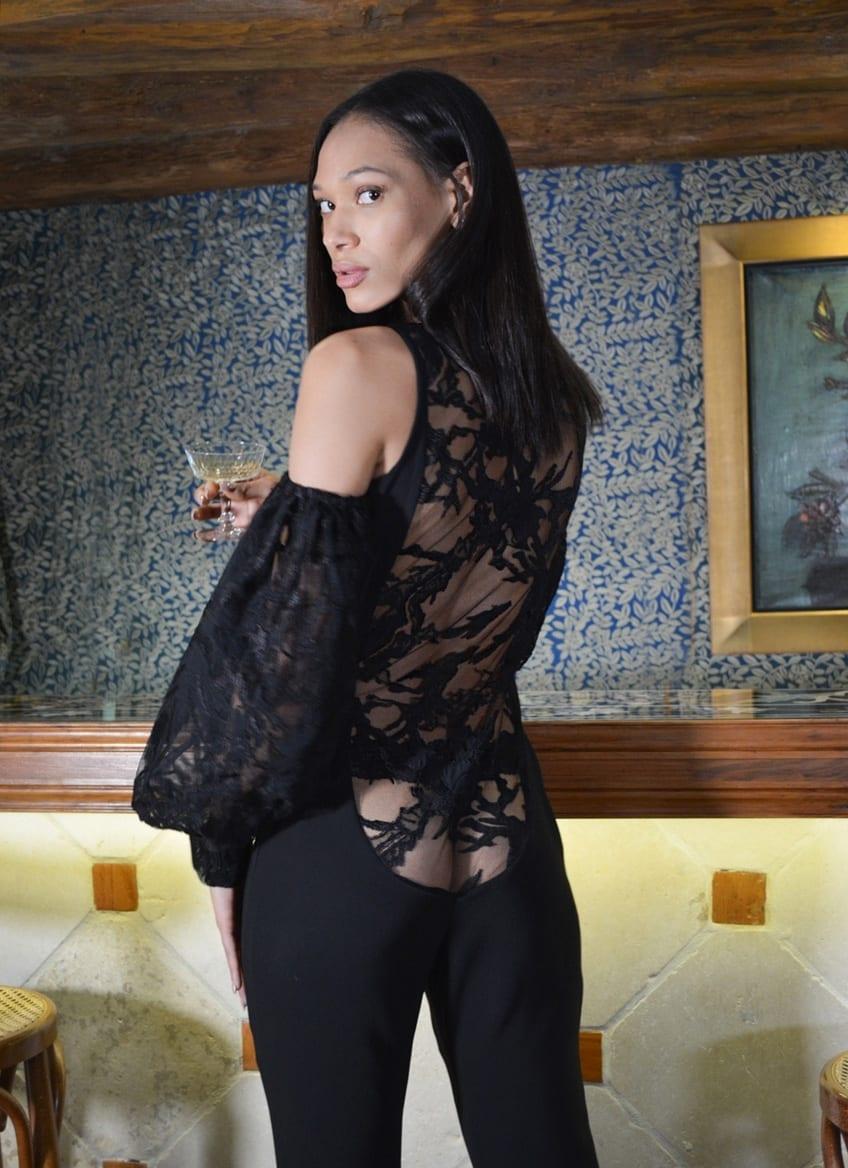 Combinaison pantalon en dentelle noire. Profond décolleté dans le dos. Création glamour pour les fêtes de fin d'année par le couturier parisien Erik Schaix.