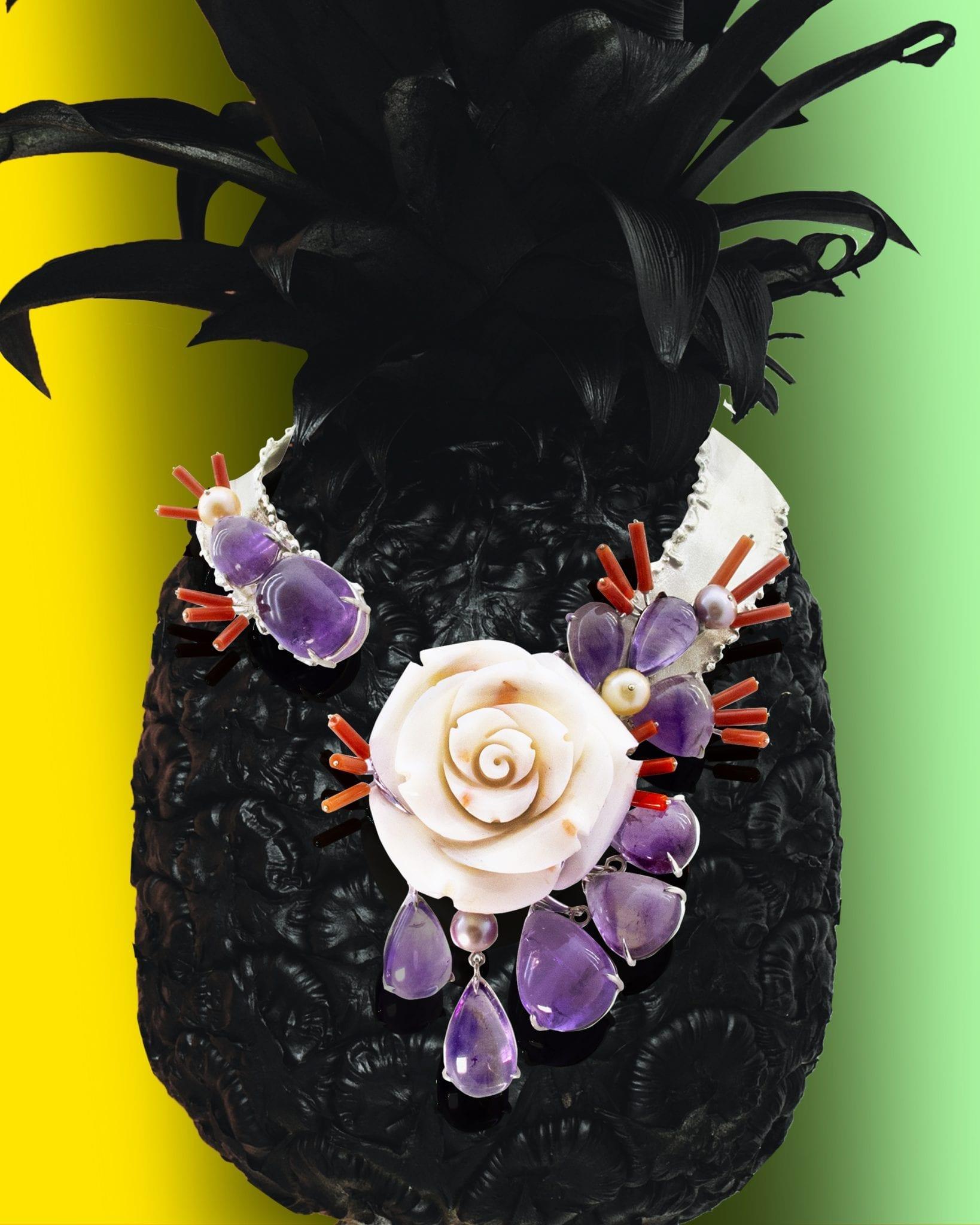 Collier ethnique en argent rigide satiné mat et granité brillant. Importante fleur de corail blanc entourée de cabochons d'améthystes mobiles et fixes, de perles de rivières rose et mauves, picots de corail rouge.