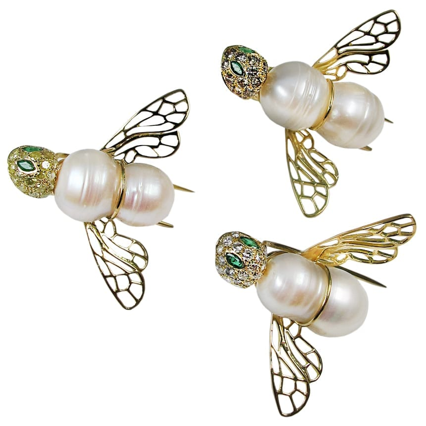 Body in freshwater pearl - wings in 18k yellow gold - head paved with diamonds and emerald eyes.