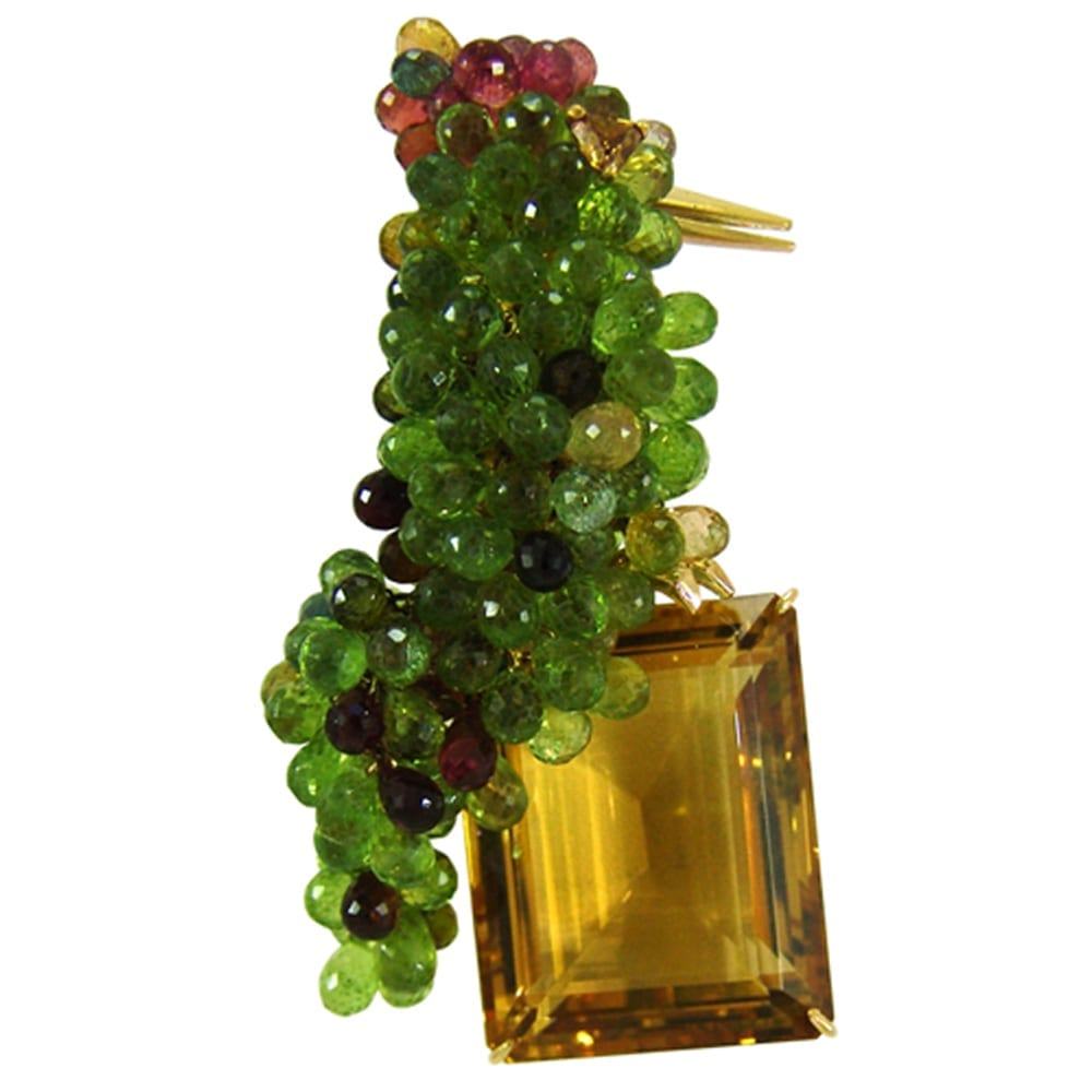 Brooch made of peridots, multicolored tourmalines, citrines and diamond eye mounted on 18k yellow gold.