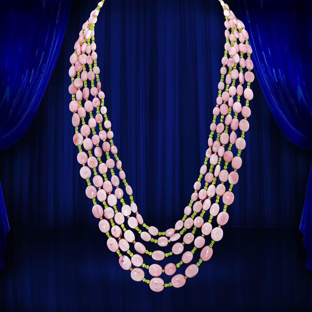 Chute 5 rangs en opales roses et boules de péridots entrecoupées de boules facettées et de viroles d'or jaune. Fermoir demi bombé en or jaune et croisillons d'or blanc serti de diamants.