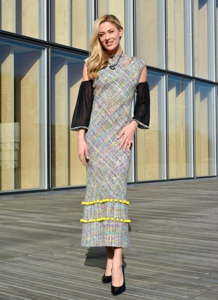 Robe longue en tweed avec manches en soie noire et 3 bandes de pompons décoratifs jaunes. Dos nu plongeant.